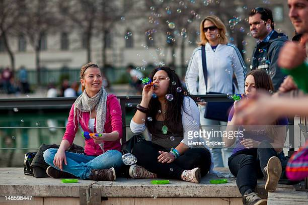 people playing with soap bubbles at erzsebet ter. - merten snijders stockfoto's en -beelden