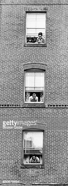 People poke their heads out of windows on Salem Street in Boston's North End on May 31 1971