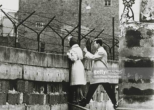 April 1962 A West Berlin girl accompanied by her boyfriend stands precariously looking over the Berlin Wall to talk to her mother a resident of East...