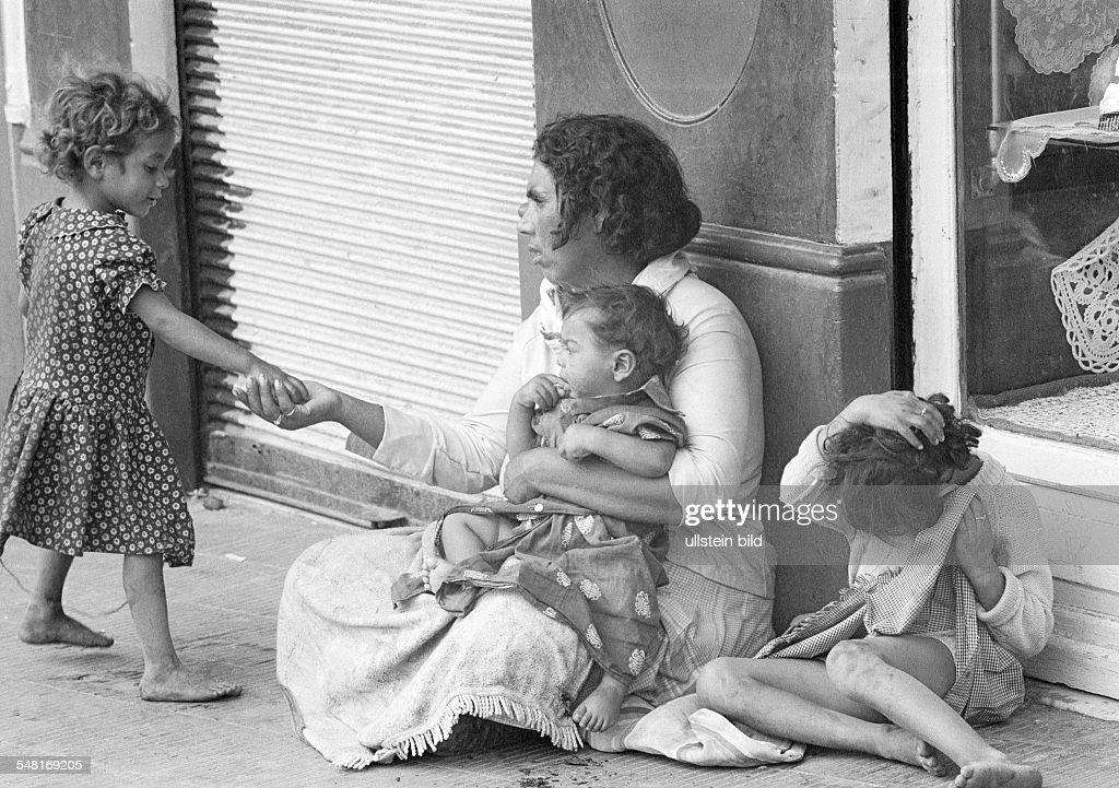 people, poorness, beggar-woman sits at the roadside with three children, a girl presents her a pittance, aged 35 to 45 years, aged 1 to 2 years, aged 4 to 6 years, Spain, Valencia - 15.08.1977 : News Photo