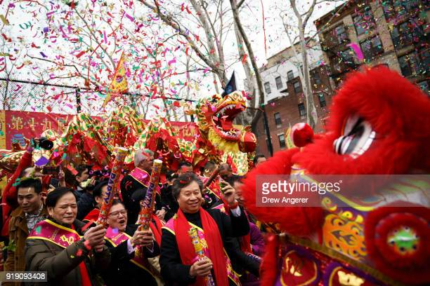 People pop confetti during a firecracker ceremony and cultural festival to mark the first day of the Lunar New Year in Chinatown neighborhood in...
