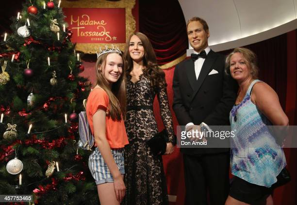 People pose alongside wax figures of Princess Catherine and Prince William at Maddam Tussauds on December 19 2013 in Sydney Australia
