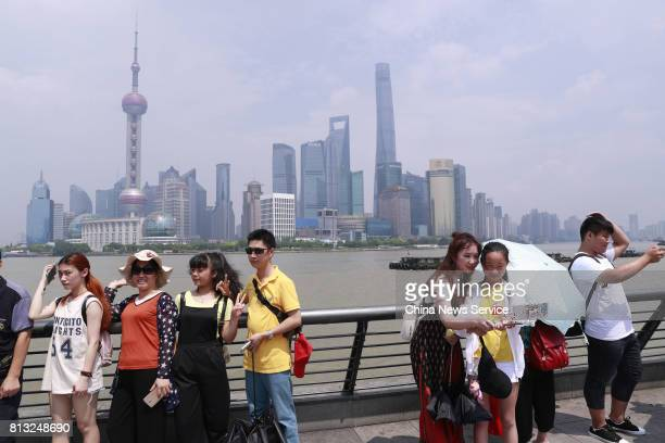People pose and take selfies at The Bund on July 12 2017 in Shanghai China The dog days of summer start from July 12 in China Shanghai released on...