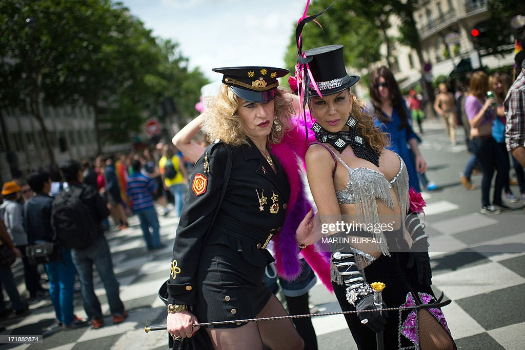 People pose as they parade during the homosexual, lesbian, bisexual and transgender (HLBT) visibility march, the Gay Pride, on June 29, 2013 in Paris, exactly one month to the day since France celebrated its first gay marriage.