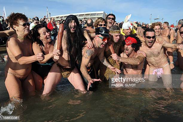 People pose as they take part in a traditional bath to mark the end of the year on December 31 2012 on a nudist beach in Le Cap d'Agde southern...