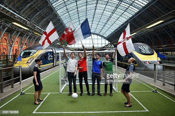 People pose fling the flags of England, Wales, France and Northern Ireland on a mini football pitch on the station platform at St Pancras station in...