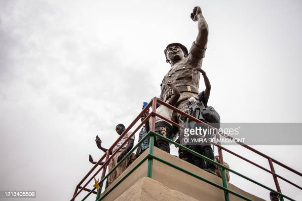 People pose for a photo beneath the second bronze statue of Burkina Faso's former President Thomas Sankara who was killed on October 15 at his...