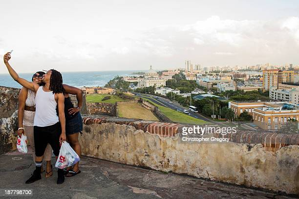 People pose for a photo in front of Old San Juan the center for Puerto Rican tourism on November 12 2013 in San Juan Puerto Rico The island territory...