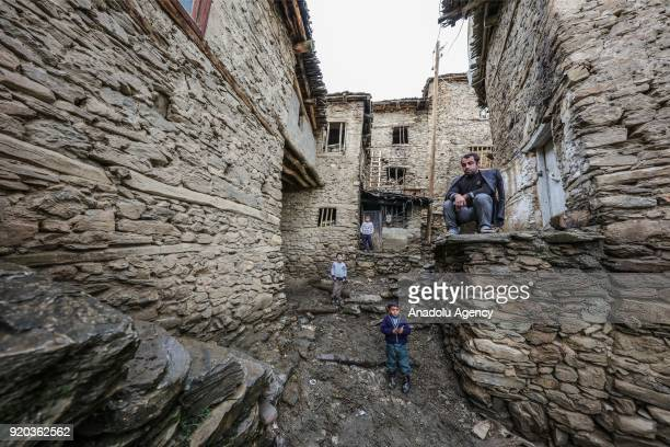 People pose for a photo in front of stone houses at their village at Hizan district in the southeastern province of Bitlis Turkey on February 18 2018...