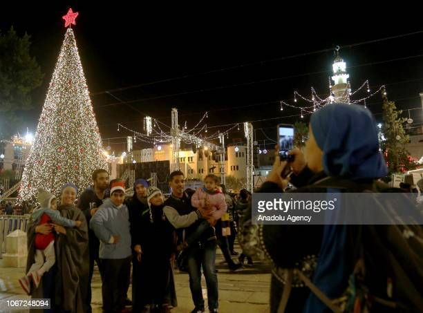 People pose for a photo in front of the illuminated Christmas Tree as streets and avenues near the Church of the Nativity which is traditionally...