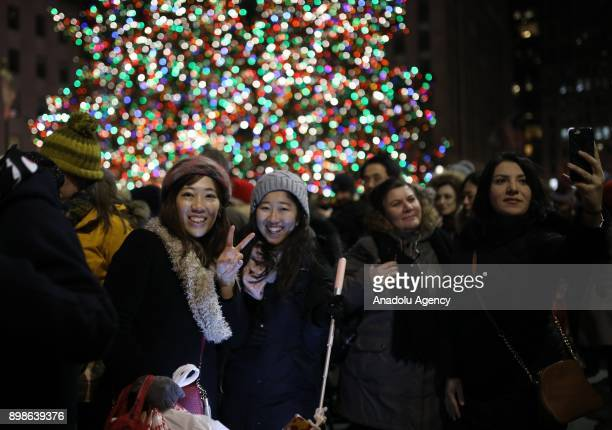 People pose for a photo in front of the illuminated the Christmas tree at Rockefeller Center on on December 26 2017 in New York City Christmas tree...
