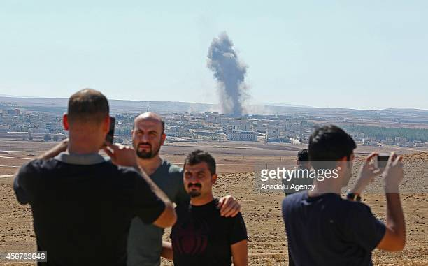 People pose for a photo in Suruc district of Sanliurfa as the smoke rises from Ayn al-Arab city of Syria after the US-led coalition bombed the...