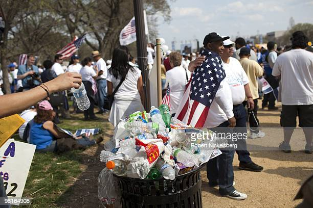People pose for a photo near a garbage bin with plastic bottles and waste in front of the US Capital Building during a rally for immigration reform...
