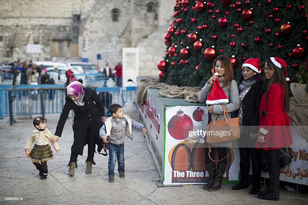 People pose for a photo next to a Christmas tree outside the Church of the Nativity, traditionally believed to be the birthplace of Jesus Christ, on December 25, 2013 in Bethlehem, West Bank. Every Christmas pilgrims travel to the church where a gold star embedded in the floor marks the spot where Jesus was believed to have been born.