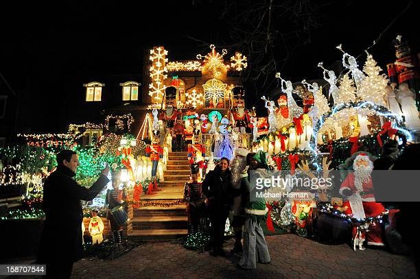 People pose for a photo with a man dressed as Santa Claus in front of a decorated house on Christmas Eve December 24, 2012 in the Dyker Heights...