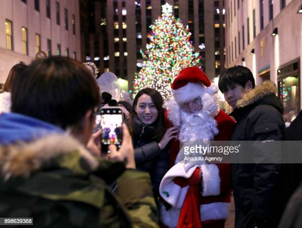 People pose for a photo with Santa in front of the illuminated the Christmas tree at Rockefeller Center on on December 26 2017 in New York City...