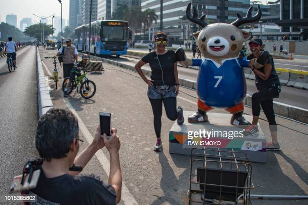 People pose for a photograph with Atung one of the official mascots for the 2018 Asian Games in Jakarta on August 12 2018