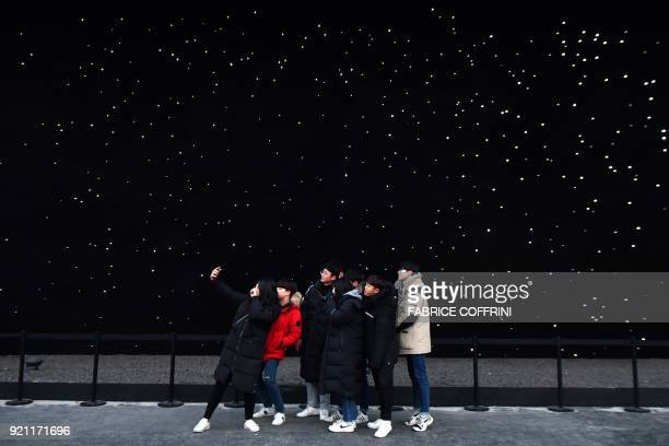 TOPSHOT People pose for a selfie at the Olympic Park during the Pyeongchang 2018 Winter Olympic Games in Pyeongchang on February 20 2018 / AFP PHOTO...