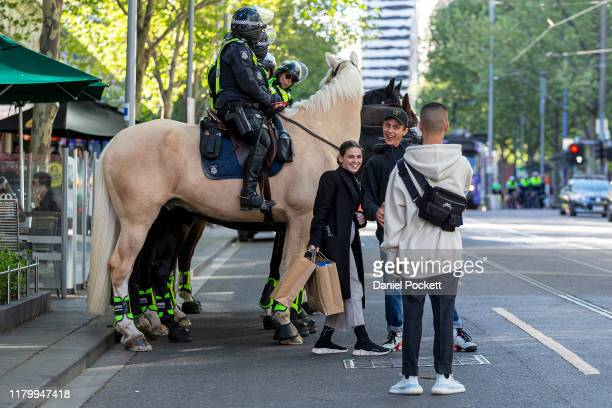 People pose for a selfie in front of police horses during a protest on October 09, 2019 in Melbourne, Australia. The event was organised as part of...