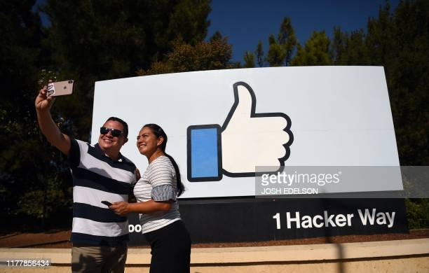TOPSHOT People pose for a selfie in front of the Facebook like sign at Facebook's corporate headquarters campus in Menlo Park California on October...