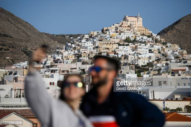 People pose for a selfie on the upper deck of a ferry from the port of Piraeus in Athens to the Island of Mykonos, Greece, stopping here at Siros...