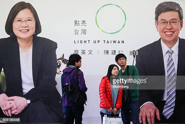 People pose for a 'selfie' photograph in front a poster featuring Tsai Ingwen presidential candidate and chairman of the Democratic Progressive Party...