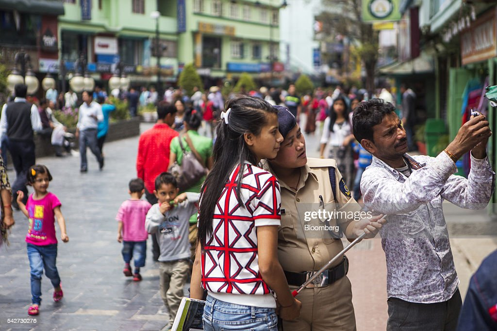 People pose for a selfie photograph on Mahatma Gandhi Road in Gangtok, India, on Tuesday, May 3, 2016. Year-on-year growth in Asia's third-largest economy accelerated in the first three months of 2016 to 7.9 percent. Photographer: Prashanth Vishwanathan/Bloomberg via Getty Images
