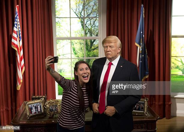 """People pose for a """"selfie"""" photograph with a waxwork model of US President-elect Donald Trump, during a photocall to promote its unveiling at Madame..."""