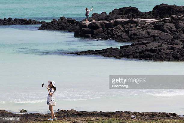 People pose for a selfie photographs on a beach in Jeju South Korea on Sunday June 28 2015 South Koreaâs 15 trillion won extra budget will channel...