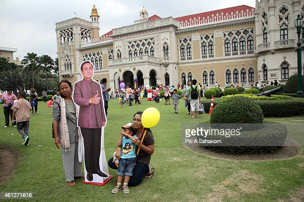 People pose for photograph with a Prime Minister Prayut Chanocha cardboard cutout during National Children's Day at The Government House in Bangkok...
