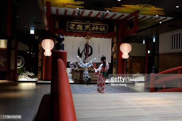 People pose for photographs in front of an imitation shrine inside the Solaniwa Onsen spa at Osaka Bay Tower during a media tour in Osaka, Japan, on...