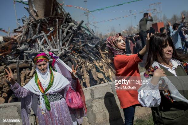 People pose for photographs in front of the Nowruz fire during Nowruz festivities on March 21 2018 in Diyarbakor Turkey Nowruz meaning new day is...
