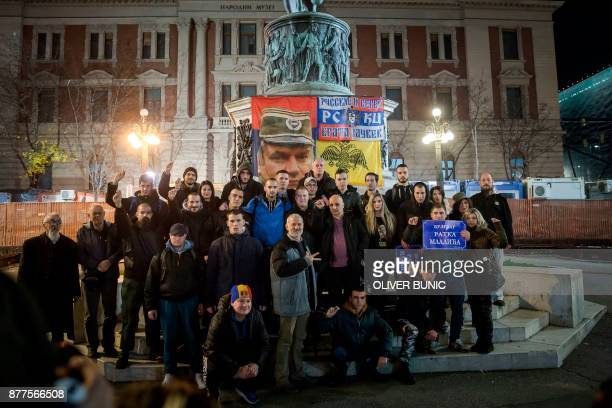 People pose for photographs in front of the statue of Prince of Serbia Mihailo Obrenovic and a flag depicting Ratko Mladic as they hold placards...