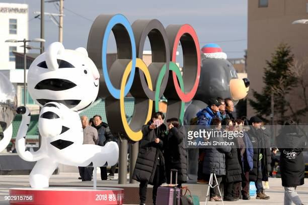 People pose for photographs with the Olympic Rings and mascots outside Gangneung station ahead of one month to go to the PyeongChang Winter Olympics...
