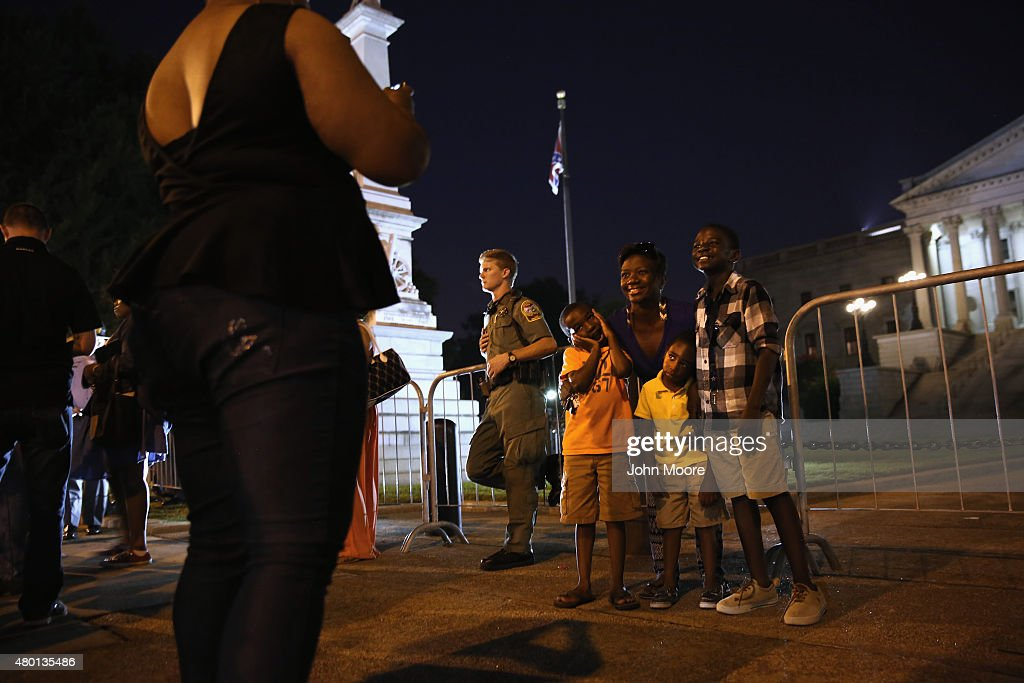 People pose for photos as the Confederate 'Stars and Bars' flies in front of the South Carolina statehouse on its last evening on July 9, 2015 in Columbia, South Carolina. South Carolina Governor Nikki Haley signed a bill to remove the Confederate flag from the statehouse grounds Friday morning.