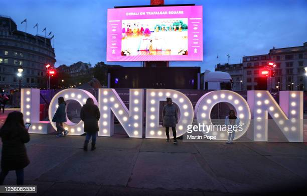People pose for photos by an illuminated sign spelling out London during Diwali celebrations in Trafalgar Square on October 23, 2021 in London,...