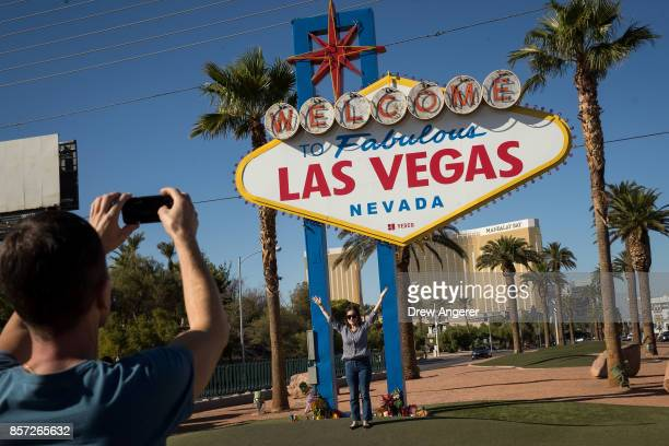 People pose for photos by the 'Welcome to Fabulous Las Vegas' sign just south of the Mandalay Bay Resort and Casino October 3 2017 in Las Vegas...