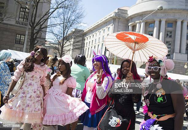 People pose for photos dressed as Japanese characters during the 55th Annual Sakura Matsuri Japanese Street Festival in Washington DC April 11 2015...