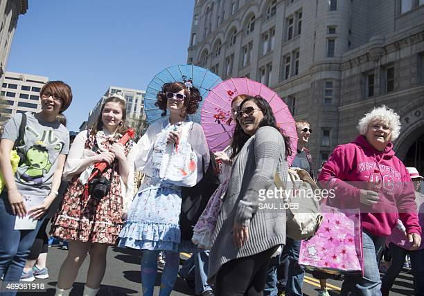 People pose for photos dressed in traditional Japanese clothing during the 55th Annual Sakura Matsuri Japanese Street Festival in Washington DC April...