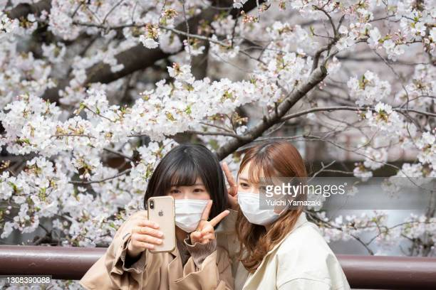 People pose for photos during the cherry blossom bloom on March 22, 2021 in Tokyo, Japan. On March 14, the Japan Meteorological Corporation declared...