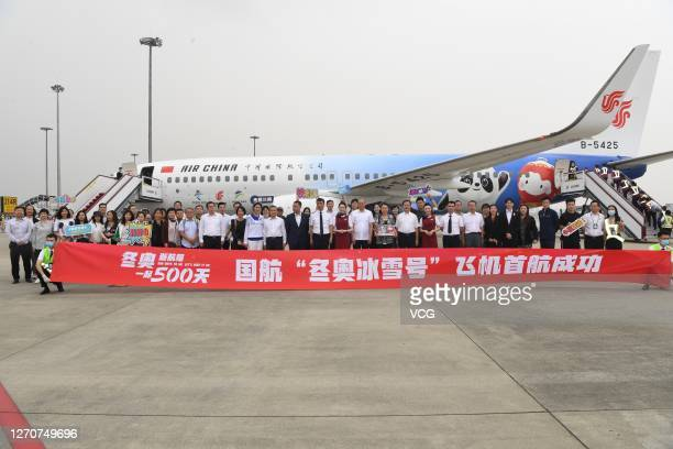 People pose for photos in front of a newly painted Boeing 737 aircraft of Air China with patterns of the emblems and mascots of Beijing 2022 Winter...