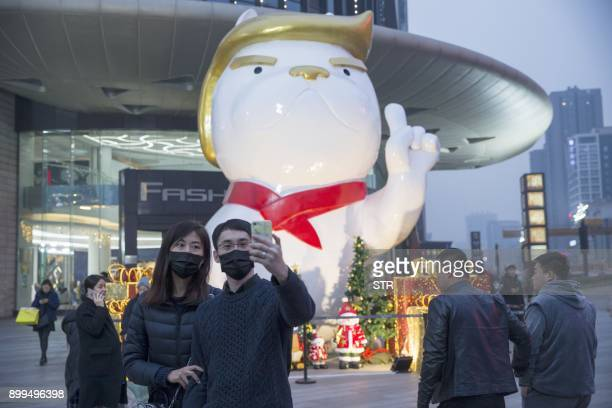 People pose for photos in front of a statue of a dog with a resemblance to US President Donald Trump outside a shopping mall in Taiyuan in China's...