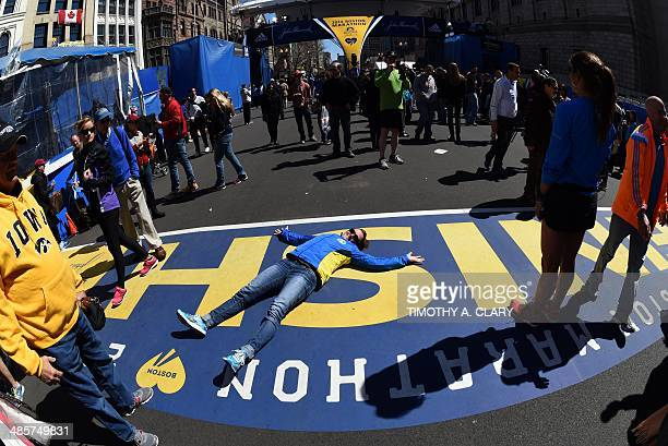 People pose for photos on the the finish line on the eve of the 2014 Boston Marathon April 20 2014 in Boston Massachussetts The Boston Marathon...