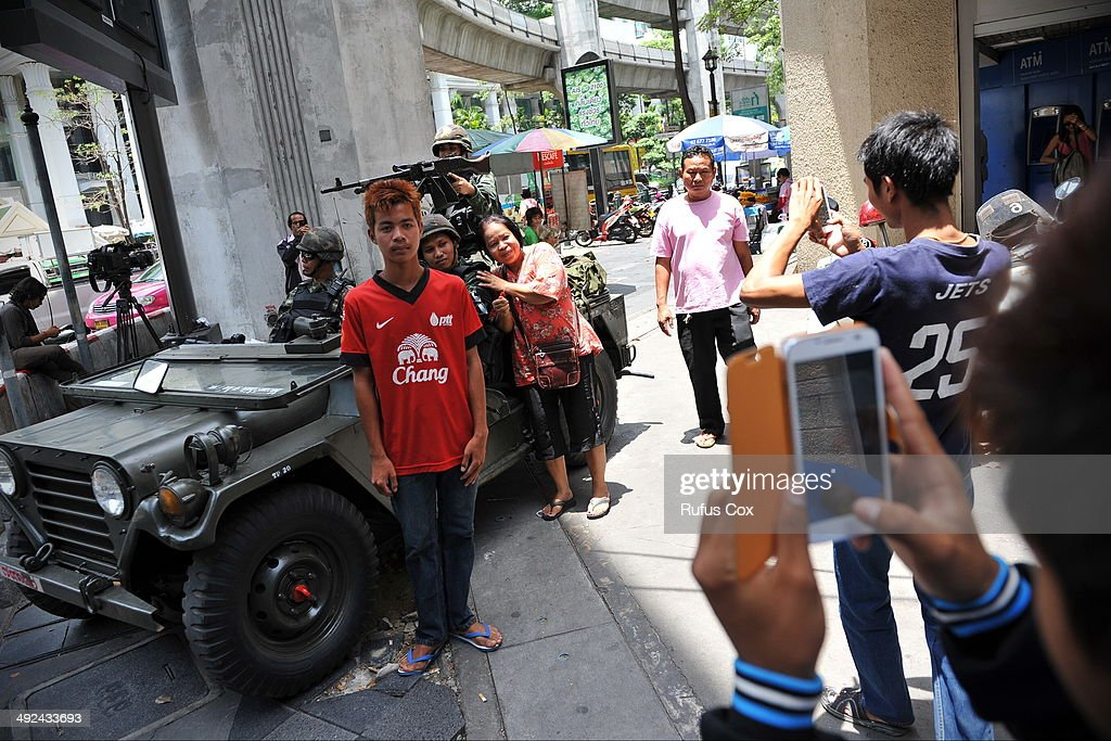 People pose for photos with Thai Army soldiers deployed on a downtown street after martial law was declared on May 20, 2014 in Bangkok, Thailand. The army imposed martial law across Thailand amid a deepening political crisis that has seen six months of protests and claimed at least 28 lives.