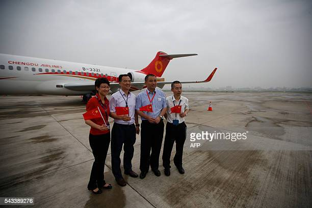 People pose for pictures as an ARJ21700 China's first domestically produced regional jet arrives at Shanghai Hongqiao Airport after making its first...