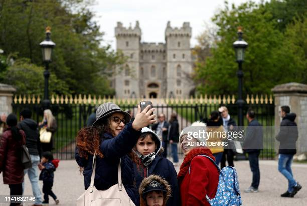 People pose for pictures at the Long Walk entrance to Windsor Castle in Windsor, west of London on May 6 after the announcement that Britain's...