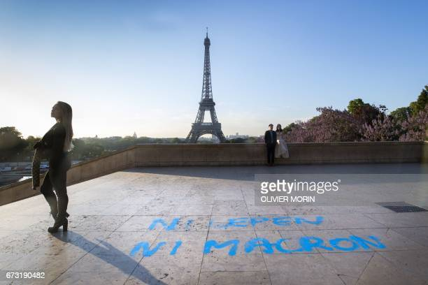 People pose for pictures in front of the Eiffel Tower at the Trocadero plazza where a graffiti on the ground refering to the second round of the...