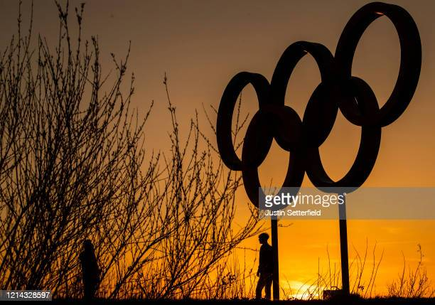 People pose for pictures in front of the Olympic rings in the Olympic Park in Stratford as Tokyo Olympics organisers are considering options to delay...