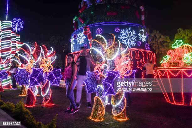 People pose for pictures next to Christmas decorations in Medellin Colombia on December 4 2017 According to EPM who is in charge of installing the...