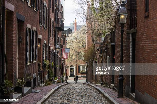 People pose for pictures on Acorn Street in the Beacon Hill neighborhood of Boston Massachusetts on Wednesday April 1 2020 Governor Charlie Baker...